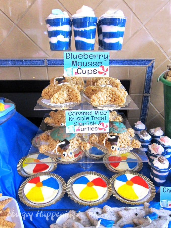 Beach themed party food including blueberry mousse cups, caramel rice krispie treat sea life, and beach ball cheesecakes.