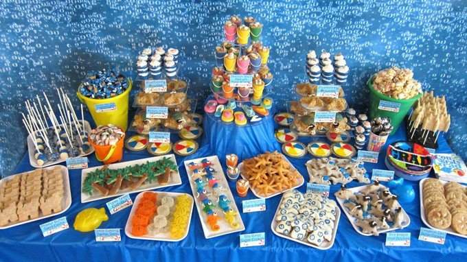 Beach themed party food ideas including beach ball cheesecakes, sea life gumdrops, chocolate beach pails, and decorated cookies galore.