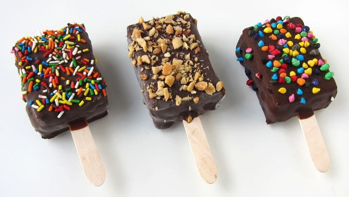 Brownie Ice Cream Sandwiches dipped in chocolate are decorated with sprinkles, nuts, and rainbow chips.