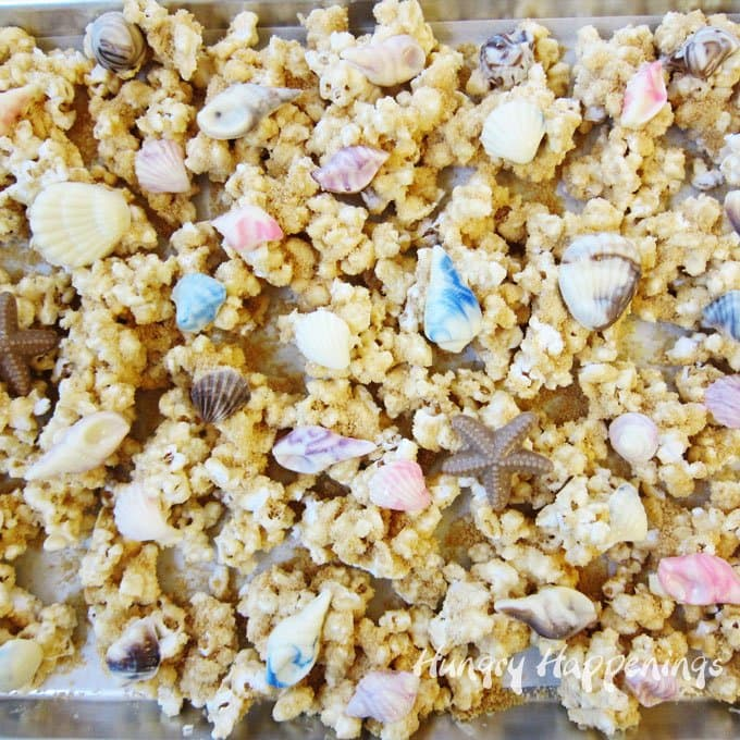 Pool party snacks - peanut butter popcorn sprinkles with sandy cookie crumbs topped with chocolate shells.