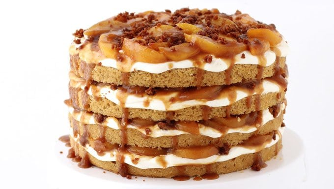 Naked Peach Cobbler Layer Cake is loaded with caramelized peaches, cheesecake fluff, crispy brown sugar cake crumbles, and caramelized peaches.