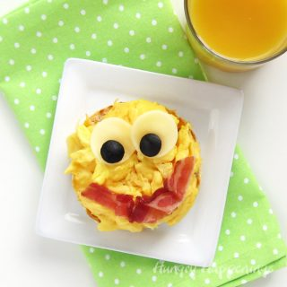 Send your kids back to school with this fun breakfast. It's so easy to turn an open-faced breakfast sandwich into this Smiley Face Egg Sandwich.