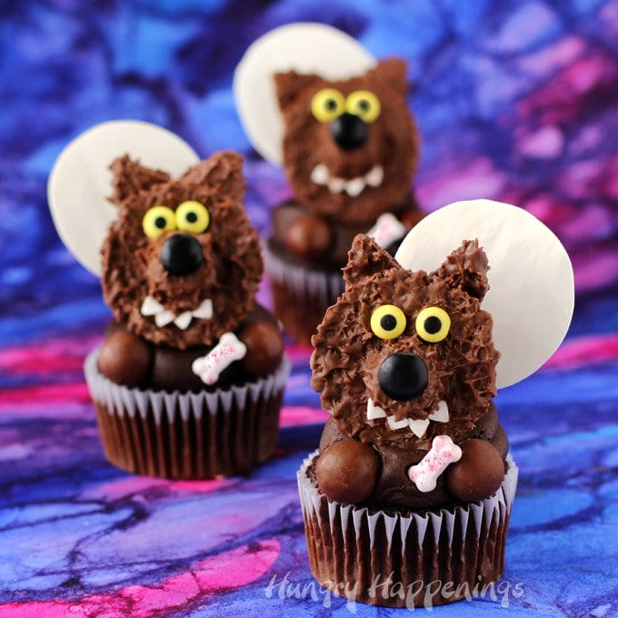 Reese's Cup Werewolf Cupcakes decorated with chocolate frosting, a Reese's Peanut Butter Cup, Whoppers, a candy bone, and a white chocolate moon.
