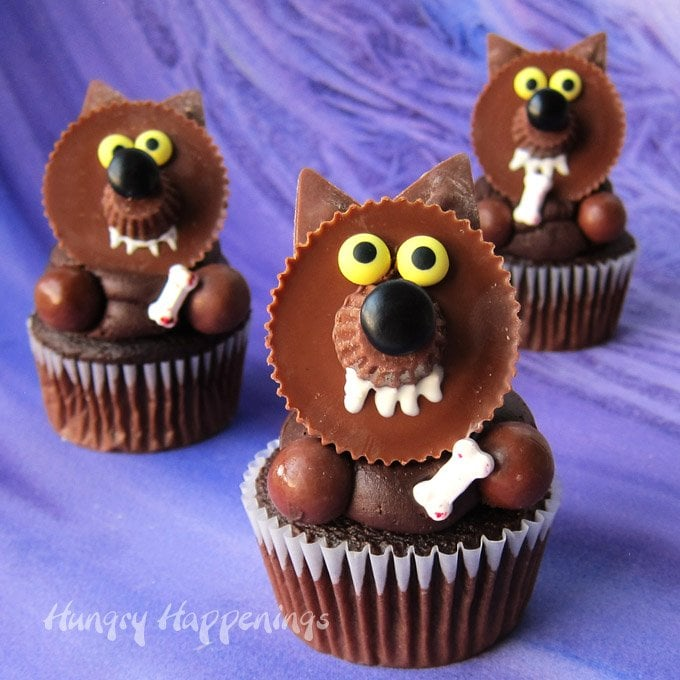 Reese's Cup Werewolf cupcakes decorated with a mini Reese's Cup snout, a Black M&M nose, yellow candy eyes, white chocolate fangs, malt ball arms, and a candy bone.