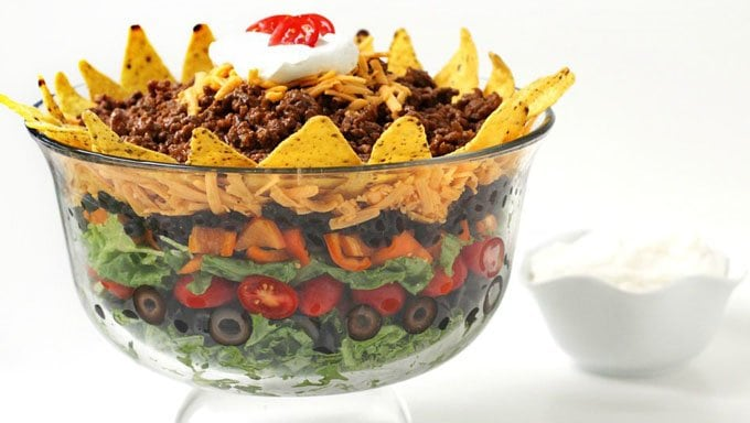 Colorful layers of lettuce, olives, tomatoes, peppers, beans, cheese, tortilla chips, beef and sour cream served in a trifle bowl.