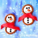 You will have so much fun building these cute Frosty Snowman Pretzels with Candy Clay Scarves in the warmth of your kitchen this winter. Each salty and sweet treats is perfect for Christmas or any snowy day.