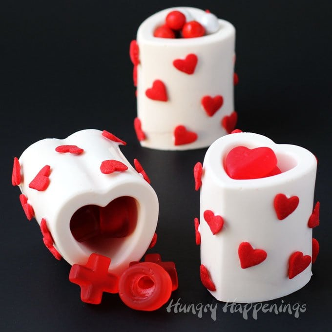 You won't believe how easy it is to make your own homemade Chocolate Heart Cups using a silicone mold. Just melt, fill, and chill then add some heart sprinkles to make them pretty and fill them with your favorite Valentine's Day candy. Kids and adults will love them.