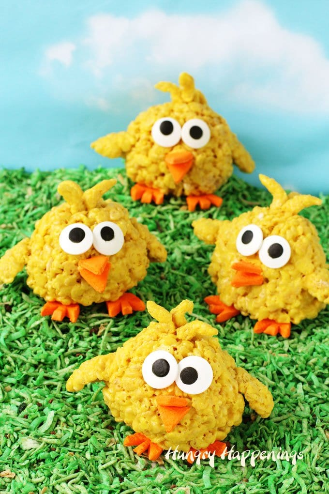 Bright yellow rice krispies treats are transformed into adorable little baby chicks for Easter with cereal treat wings and feathers and orange circus peanut feet and beaks and big candy eyes.