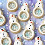 white chocolate topped snowman cookies have clear candy bellies and are filled with blue and white snowflake sprinkles