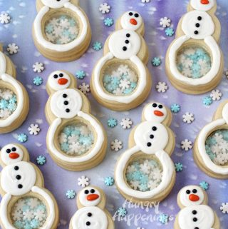 snowflake filled snowman cookies arranged on a blue watercolor background with snowflake sprinkles scattered in between the cookies