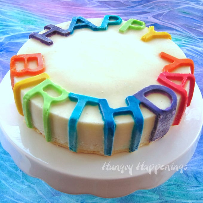"Brightly colored rainbow ""Happy Birthday"" cheesecake is naturally gluten free."