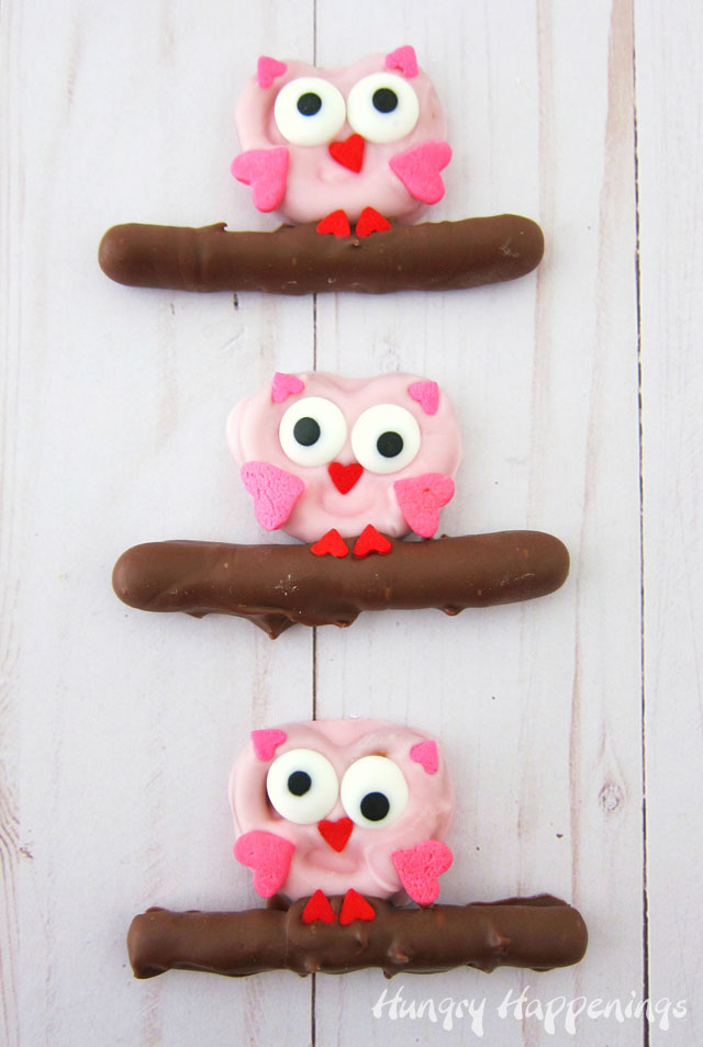 Dip mini pretzel twists in pink candy melts then add heart sprinkles and candy eyes to transform them into owls.