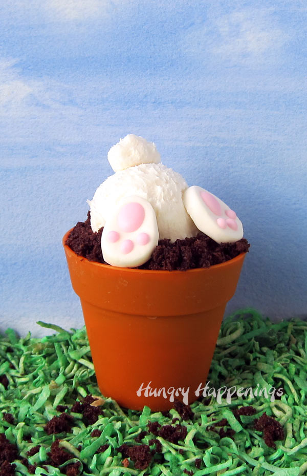 Chocolate cupcakes topped with chocolate ganache and cake crumbs are decorated with frosting bunny butts for Easter.
