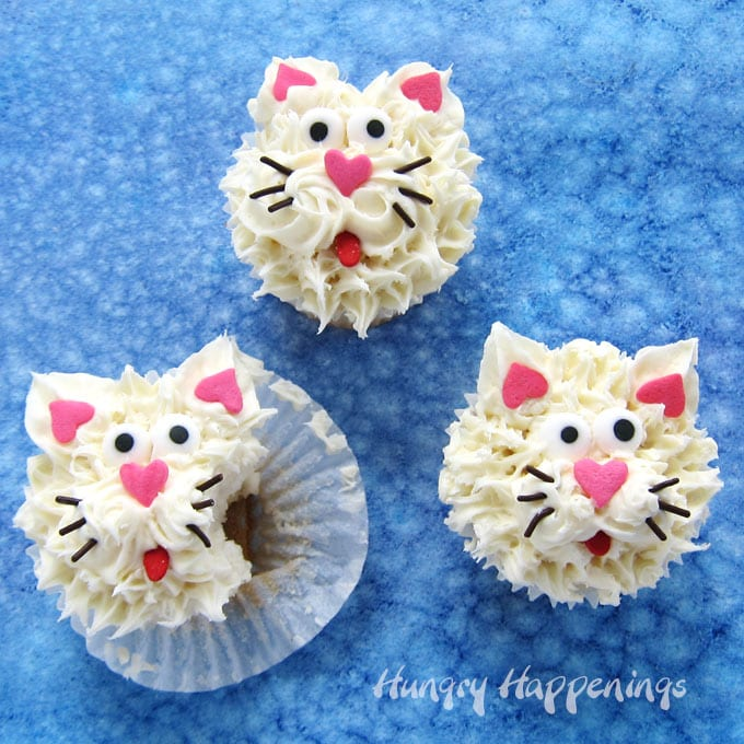 Cute cat cupcakes frosted with white vanilla frosting and decorated with heart sprinkles, chocolate jimmies, and candy eyes.