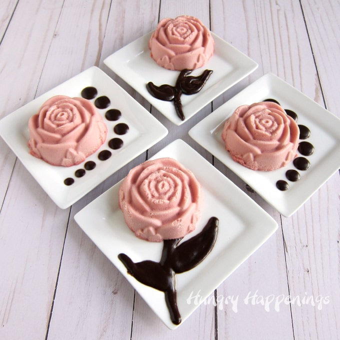 Pink cheesecake roses flavored with raspberry puree and decorated with chocolate ganache stems, leaves, and dots.