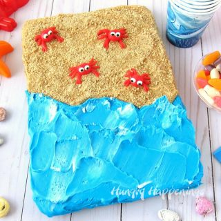 Beach cake brownie topped with peanut butter frosting and cookie crumb sand, a swirl of blue and white frosting water, and a few red candy crabs.