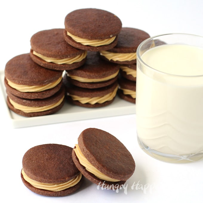 peanut butter fudge filled chocolate cookies stacked up on a white plate set next to a glass of milk