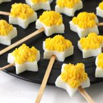 Deviled eggs cut using a star shaped cookie cutter are made into lollipops.