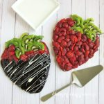 Fruit Pizza Strawberry - chocolate cookies cut into strawberry shapes topped with cream cheese frosting and fresh strawberries and kiwi. One is coated in dark chocolate ganache and drizzled with white chocolate.