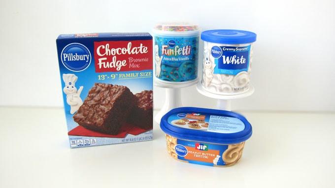 Pillsbury™ Chocolate Fudge Brownie Mix, Pillsbury™ Jif® Peanut Butter Frosting, Pillsbury™ Creamy Supreme Vanilla Frosting, and Pillsbury™ Funfetti Aqua Blue Vanilla Frosting