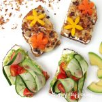 Avocado toast with cucumbers, tomatoes, and dill accompanied by Tropical Toast topped with bananas, toasted coconut, chocolate, almonds, mango and papaya flowers.