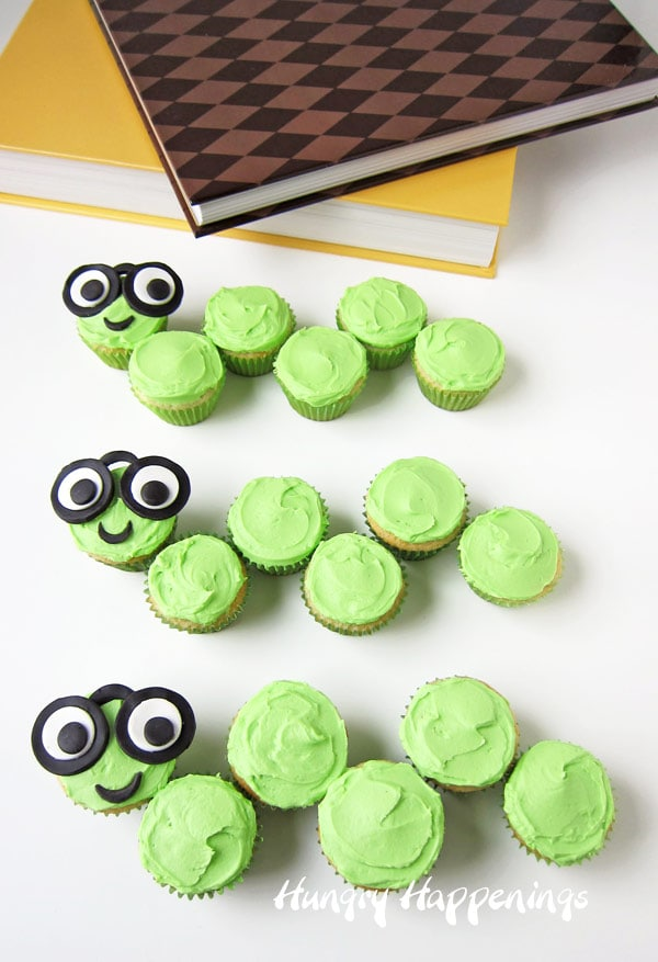 mini cupcakes frosted with lemony green frosting are arranged to look like bookworms wearing glasses made from candy clay