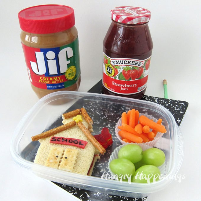 Make a back to school Jif Peanut Butter and Smucker's Strawberry Jam sandwich that looks like a schoolhouse with grapes and carrots.