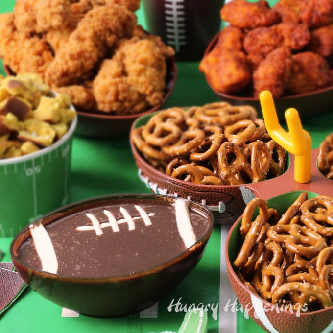 football party tablescape featuring a chocolate dip football, mini pretzel twists, chicken strips, and buffalo chicken nuggets