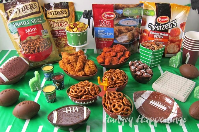 game day tablescape decorated with a green football field tablecloth and football shaped bowls filled with pretzels, chocolate dip, chicken strips, buffalo chicken nuggets, and more