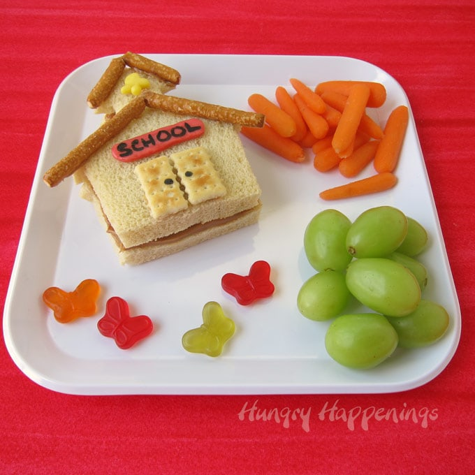 Fun kids lunch featuring a peanut butter and jelly sandwich schoolhouse, green grapes, baby carrots, and butterfly candies.