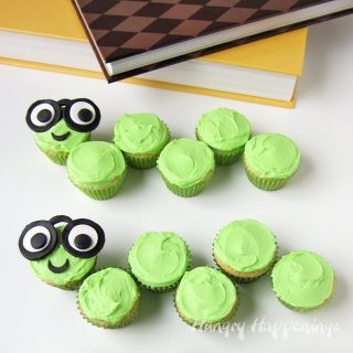 mini cupcakes frosted with bright green buttercream and arranged to look like bookworms with candy clay glasses and googly eyes sitting next to books