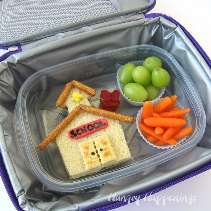 Kid's school lunch of Peanut Butter and Jelly Sandwich cut and decorated to look like a schoolhouse along with grapes and carrots.