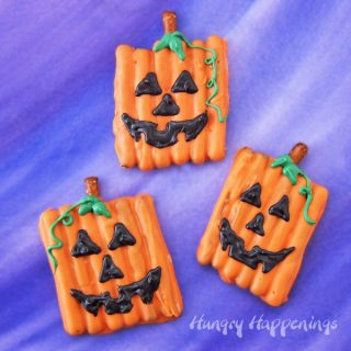 orange candy coated pretzels decorated like jack-o-lanterns