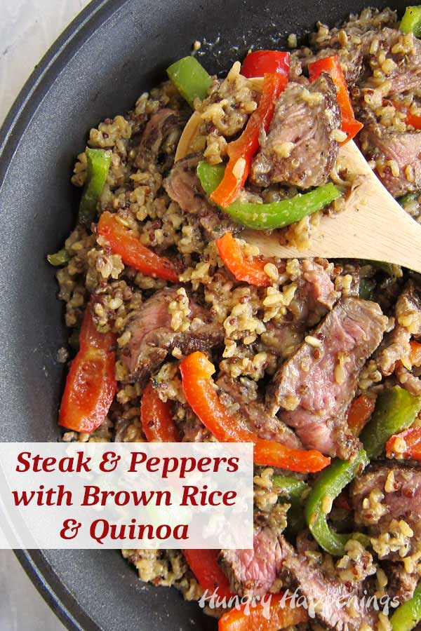 Sirloin steak with peppers and onions cooked with brown rice and quinoa in a skillet.
