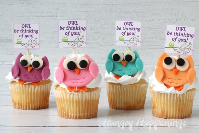 "Five owl cupcakes with tags that say, ""Owl Be Thinking Of You!"" in a row on a gray wood grain background"