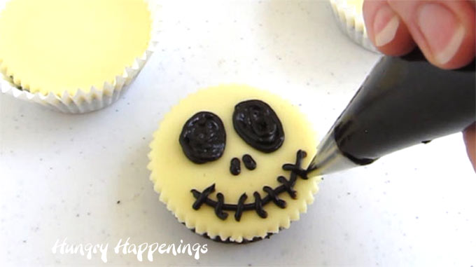 Decorate the mini cheesecake using chocolate ganache to create these Jack Skellington cheesecakes.