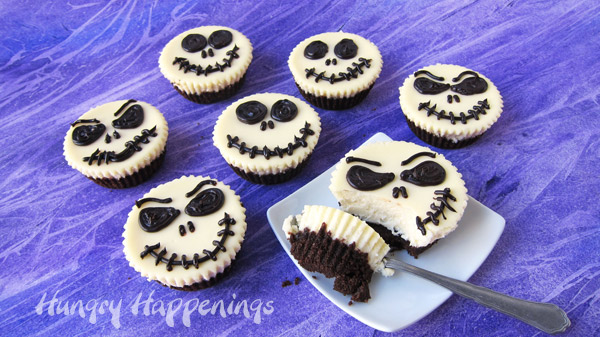Jack Skellington Cheesecakes arranged in a circle with one on a white plate with a spoonful scooped out.