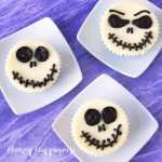 mini cheesecakes decorated to look like Jack Skellington are plated on small square white plates set on a purple watercolor backdrop