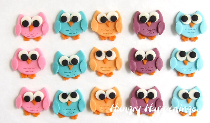 blue, pink, teal, peach, and lilac colored modeling chocolate owls lined up in three rows