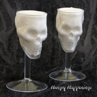 no-bake cheesecake served in skull shaped wine glasses displayed on a black watercolor background