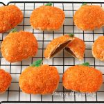 pumpkin hand pies coated in bright orange sugar set on top of a black wire cooling rack
