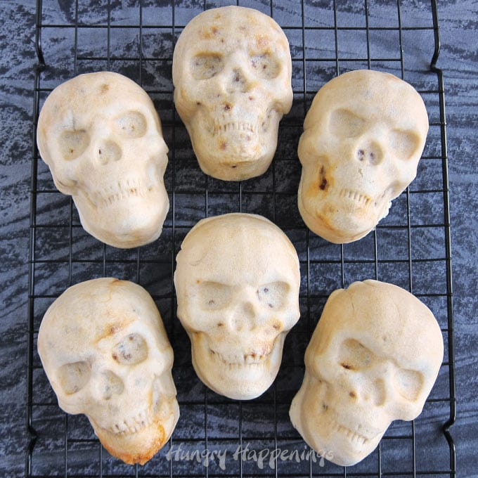 6 skull shaped burritos set on a black cooling rack on a black and grey watercolor background