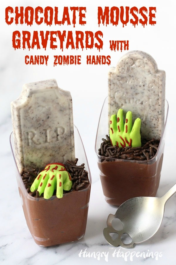vertical image of two chocolate mousse cups decorated like graveyards with royal icing zombie hands and candy tombstones. The mousse cups are sitting next to a skull spoon.
