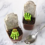 two chocolate mousse graveyards with green candy zombie hands and cookies and cream candy bar tombstones