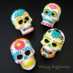 four sugar skulls decorated with colorful royal icing flowers, hearts, spider webs and more on a black background