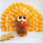 bacon ranch cheese ball decorated to look like a turkey is surrounded by cheese topped cracker feathers