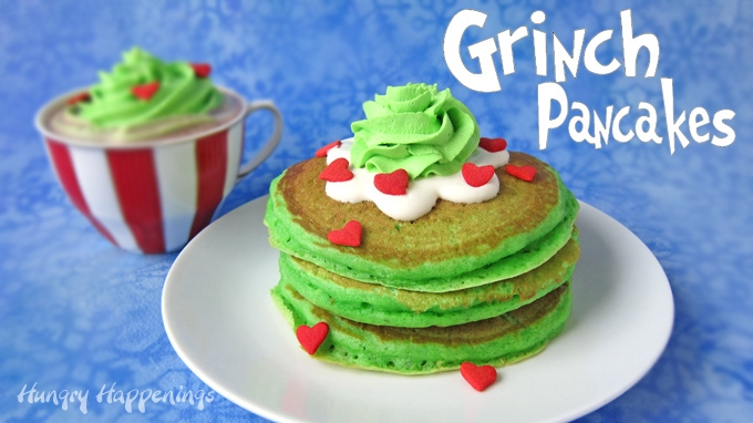 Grinch's Green Pancakes stacked on a white plate sitting next to a cup of Minty Who-Hot Chocolate.