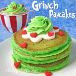 a stack of green copycake IHOP Grinch pancakes topped with cream cheese glaze, green whipped cream, and candy hearts on a white plate are set in front of a red and white striped cup filled with grinch hot chocolate