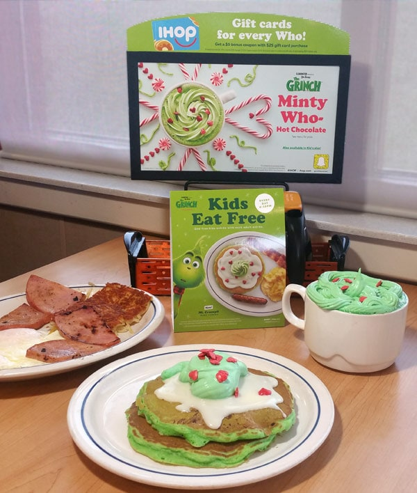 Plates of IHOP Grinch's Green Pancakes, Minty Who-Hot Chocolate, eggs and ham, sitting in front of IHOP's Grinch Menu signage