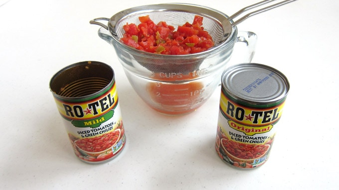 One can of RO*TEL® Mild Diced Tomatoes and Green Chilies and one can of RO*TEL® Original Diced Tomatoes and Green Chilies are set in front of a bowl of tomatoes draining through a fine mesh sieve.
